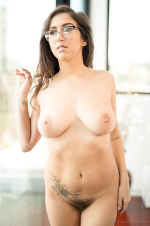 Curvy bookworm April Oneil smiles while showing juicy tits and bush in bedroom