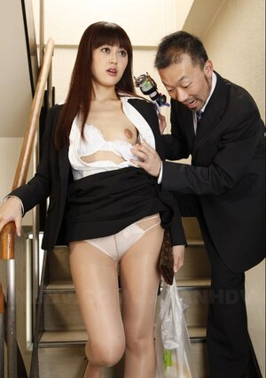 Lad in a suit takes off Asian's nylons on the stairs and aims strange toy at it
