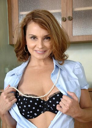 Soccer mom opens her blue shirt and poses half-naked on a stool in the kitchen