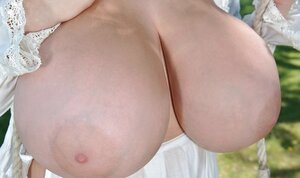 Dark-haired lady from the United Kingdom proudly demonstrates giant boobs
