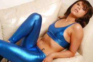 Babe wears shiny-blue clothes flashing her boobies and pussy a bit