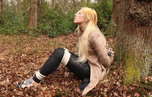 Babe with glasses can't stand up because she is hogtied by the tree